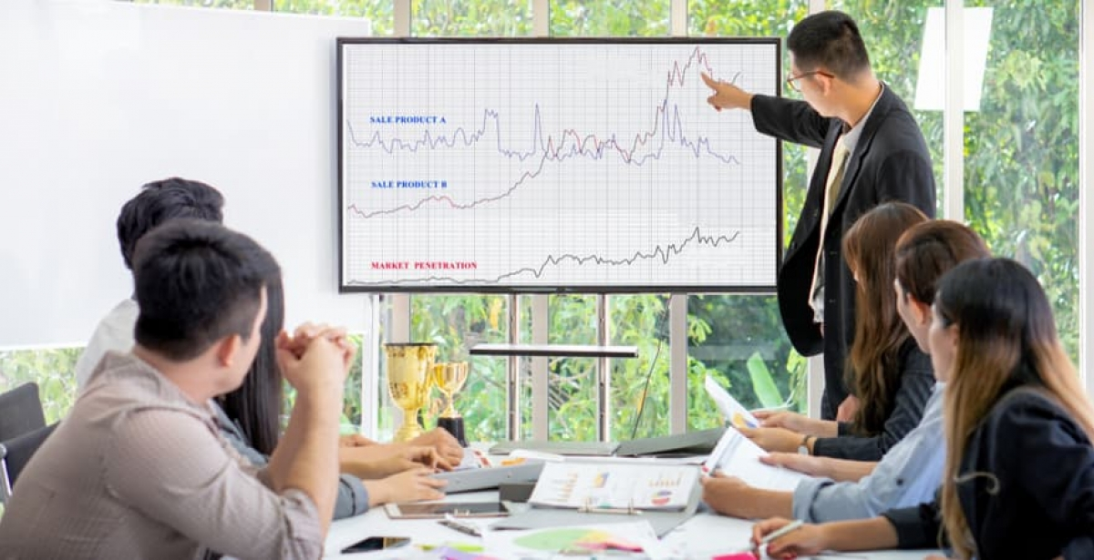 A data scientist presenting some information to colleagues on a computer screen.