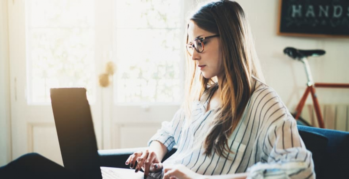 A female postgraduate student studying online in her quiet study space at home.