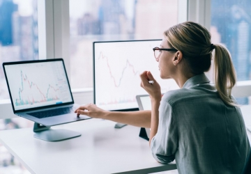 Woman analysing financial graphs and statistics on computer.